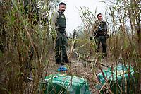 Border patrol agents look at bags of marijuana seized along the Rio Grande river, in Hidalgo, TX, on the U.S.-Mexico border, on February 2, 2017 (Photo/Scott Dalton)