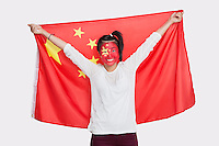 Portrait of young Asian woman with Chinese flag and painted face against white background