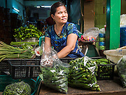 21 OCTOBER 2014 - BANGKOK, THAILAND:  A vegetable vendor in the Bangkok Flower Market. The Bangkok Flower Market (Pak Klong Talad) is the biggest wholesale and retail fresh flower market in Bangkok. It is also one of the largest fresh fruit and produce markets in the city. The market is located in the old part of the city, south of Wat Po (Temple of the Reclining Buddha) and the Grand Palace.    PHOTO BY JACK KURTZ