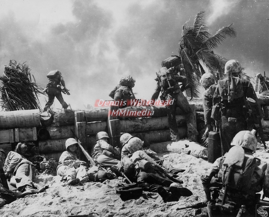 Against the withering fire of numerous Japanese machine guns in pillboxes, bunkers and dugouts on Tarawa Island, Marines scamper up and over the coconit log barricade and into the attack.