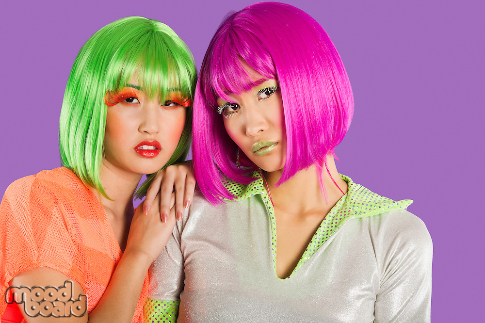 Portrait of two female friends wearing wigs against gray background
