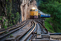 After a rain and nearing sunset, a train passes over the Krasae Viaduct near Kanchanaburi, Thailand. This track is part of the infamous Death Railway, built during WWII.