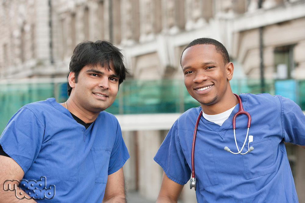Portrait of multi ethnic doctors smiling with building in background