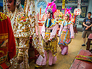 18 JANUARY 2015 - BANGKOK, THAILAND:  Performers with the Sai Yong Hong Opera Troupe walk through the Chaomae Thapthim Shrine during a performance at the Chaomae Thapthim Shrine, a Chinese shrine in a working class neighborhood of Bangkok near the Chulalongkorn University campus. The troupe's nine night performance at the shrine is an annual tradition and is the start of the Lunar New Year celebrations in the neighborhood. The performance is the shrine's way of thanking the Gods for making the year that is ending a successful one. Lunar New Year, also called Chinese New Year, is officially February 19 this year. Teochew opera is a form of Chinese opera that is popular in Thailand and Malaysia.             PHOTO BY JACK KURTZ