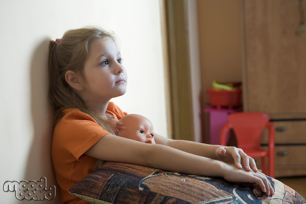 Girl sits in playroom with cushion loking up