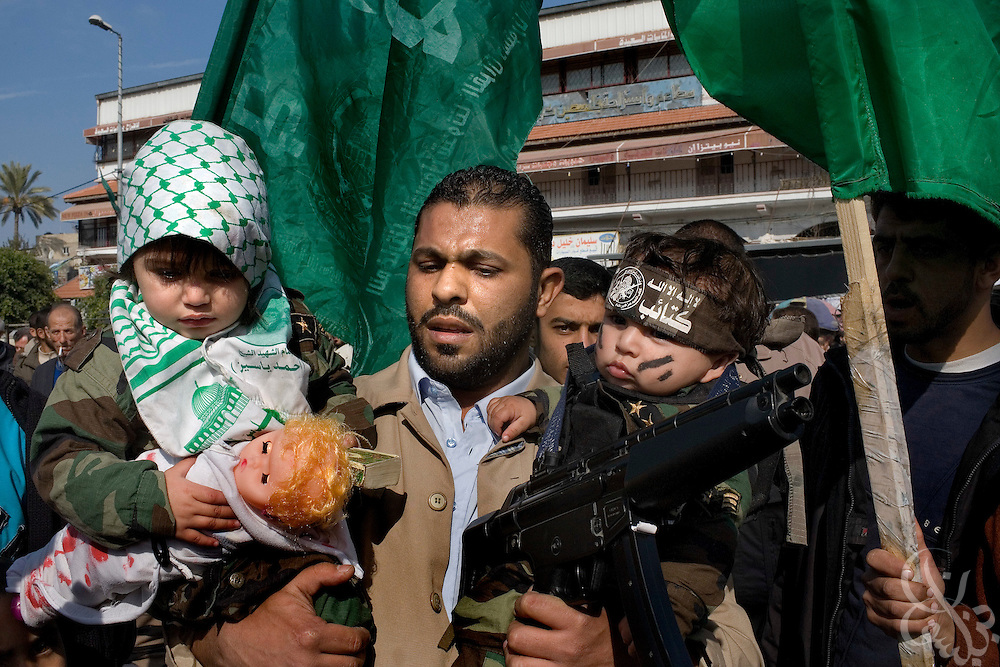 "A Palestinian man holds his two children, dressed for the occasion of a ""Victory"" parade thrown by militant Palestinian political group HAMAS January 20, 2009 in Gaza City. Several thousand marchers celebrated what HAMAS called the defeat of Israel during the recent 21 day offensive by Israeli forces against HAMAS fighters. During the operation more than 1500 Palestinians were killed and more than 4000 homes destroyed in the narrow Gaza Strip."