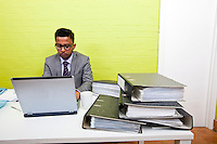Portrait of Indian Businessman working on his laptop computer at his desk