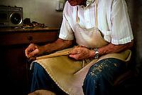 Laboratorio in cui l'artigiano lavora il legno di ulivo per ottenere utensili da cucina. l'artigiano leviga l'attrezzo con un pezzo di vetro.