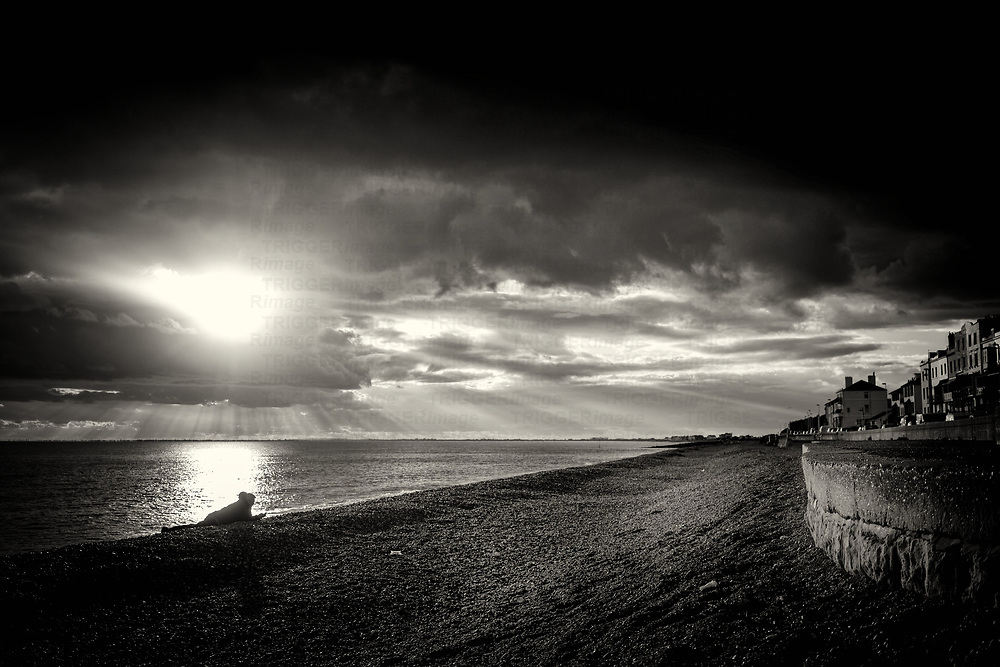 Stormy skies over the seafront in Hythe, Kent, England with male figure lying on the beach under dramatic clouds with sunset