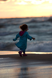 Little girl dresses in colorful clothes walking on beach