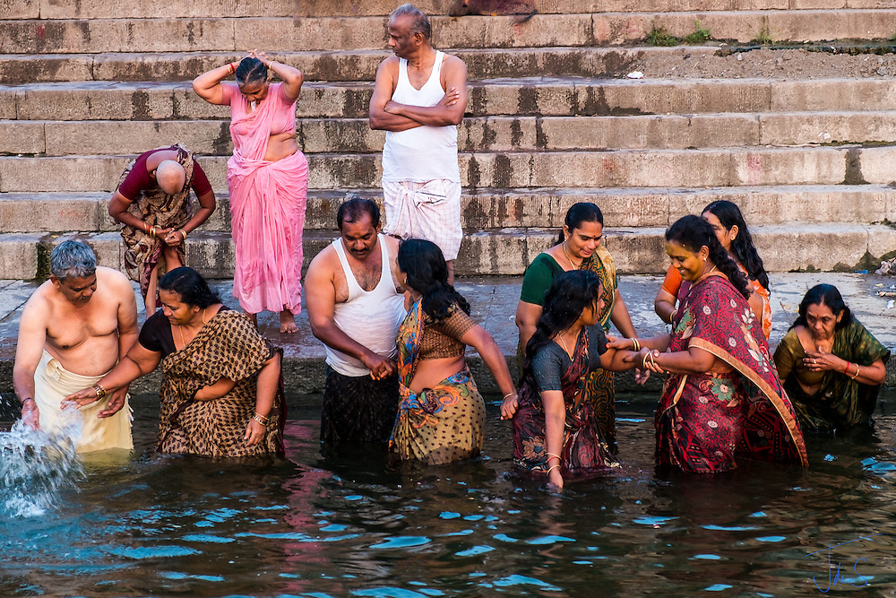 Husbands encourage their wives to take a tip in mother Ganges