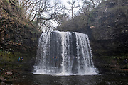 People explore and go behind the Sgwd Yr Eira Waterfall in the Afon Hepste River in Brecon Beacons Waterfall Country National Park, Wales, Powys, United Kingdom. This waterfall is famous as one of the only waterfalls in Wales that you can walk behind.  (photo by Andrew Aitchison / In pictures via Getty Images)