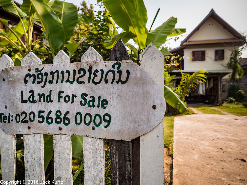 """13 MARCH 2016 - LUANG PRABANG, LAOS: A home for sale in the historic quarter of Luang Prabang. The for sale sign being in English indicates who the property is being marketed to. Luang Prabang was named a UNESCO World Heritage Site in 1995. The move saved the city's colonial architecture but the explosion of mass tourism has taken a toll on the city's soul. According to one recent study, a small plot of land that sold for $8,000 three years ago now goes for $120,000. Many longtime residents are selling their homes and moving to small developments around the city. The old homes are then converted to guesthouses, restaurants and spas. The city is famous for the morning """"tak bat,"""" or monks' morning alms rounds. Every morning hundreds of Buddhist monks come out before dawn and walk in a silent procession through the city accepting alms from residents. Now, most of the people presenting alms to the monks are tourists, since so many Lao people have moved outside of the city center. About 50,000 people are thought to live in the Luang Prabang area, the city received more than 530,000 tourists in 2014.    PHOTO BY JACK KURTZ"""