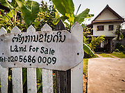 "13 MARCH 2016 - LUANG PRABANG, LAOS: A home for sale in the historic quarter of Luang Prabang. The for sale sign being in English indicates who the property is being marketed to. Luang Prabang was named a UNESCO World Heritage Site in 1995. The move saved the city's colonial architecture but the explosion of mass tourism has taken a toll on the city's soul. According to one recent study, a small plot of land that sold for $8,000 three years ago now goes for $120,000. Many longtime residents are selling their homes and moving to small developments around the city. The old homes are then converted to guesthouses, restaurants and spas. The city is famous for the morning ""tak bat,"" or monks' morning alms rounds. Every morning hundreds of Buddhist monks come out before dawn and walk in a silent procession through the city accepting alms from residents. Now, most of the people presenting alms to the monks are tourists, since so many Lao people have moved outside of the city center. About 50,000 people are thought to live in the Luang Prabang area, the city received more than 530,000 tourists in 2014.    PHOTO BY JACK KURTZ"