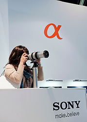 Female visitor using Sony camera and lens at Photokina digital imaging trade show in Cologne Germany