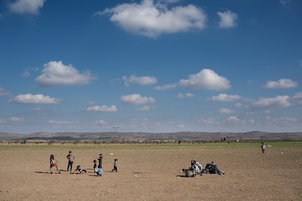 An Afghan family rests in the field behind the petrol station near Idomani. The kids enjoy the warmth of the sun and playing. In the last few months the fields near this petrol station have become a transit camp for thousands of refugees and migrants waiting to cross to Greek Macedonian border.