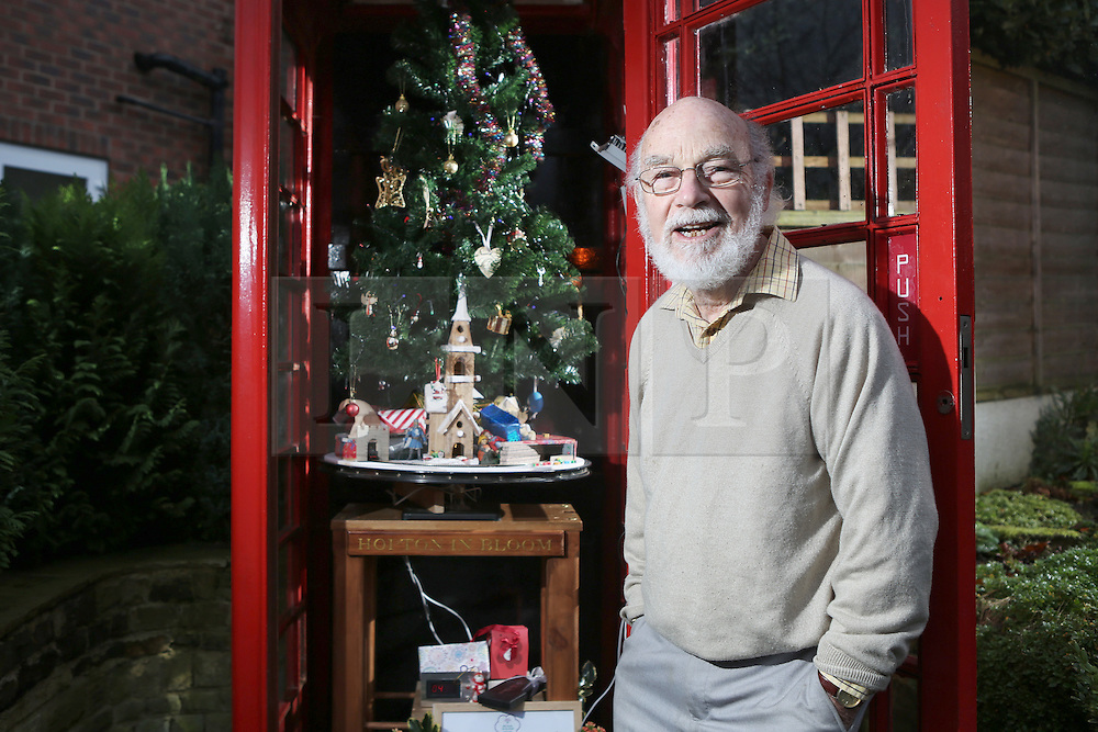© Licensed to London News Pictures. 15/12/2016. Upper Hopton, UK. John Broscombe with the phonebox he has converted into a christmas display. The phonebox in the village of Upper Hopton in West Yorkshire features a christmas tree, a toy train, which can be activated at the push of a button, and many other lights and decorations. The disused phone box bought by the community for just £1 has proved a focal point for the village – helping to promote local events and raising a smile with a series of animated displays at different times of the year. Photo credit : Ian Hinchliffe/LNP
