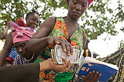 A woman receives money during a UNICEF-sponsored social cash transfer programme distribution in the village of Julijuah, Bomi county, Liberia on Tuesday April 3, 2012. Beneficiary households receive monthly transfers that vary according to the size of the household, with additional sums provided for each child enrolled in school. Families are selected for participation in the programme based on two key criteria: they must be both extremely poor and labour-constrained.
