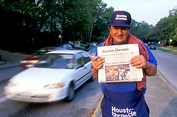 Stock photo of a man standing in the median selling Houston Chronicle newspapers