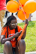 Girl on phone with balloons at the Fourth of July parade in Ames, Iowa