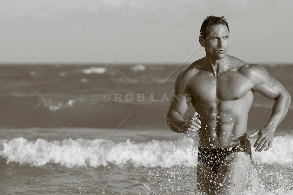 muscular man running through the ocean waves in Florida
