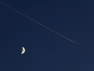 Salisbury Mills, New York - A jet airplane and its condensation trail are visible in the sky near the moon at twilight on Oct. 13, 2010.