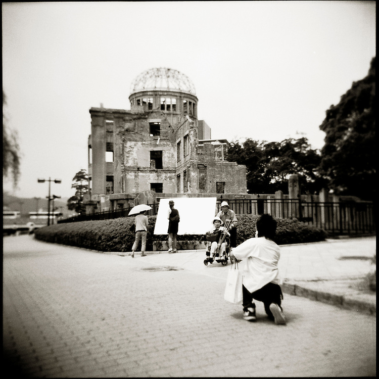 """hiroshima A-Bomb Dome Japanes tourist pose for pictures infromt of the A-Bomb Dome Text inscribed on a plaque says """"The A-bomb Dome is the ruins of the former Prefectural Industrial Promotion Hall destroyed by the the world's first A-bomb on August 6, 1945..It exploded about 600 meters above this building,taking the lives of more than 200,000 people and reducing to ashes the urban area ranging over a radius of 2 kilometers..In order to hand down this terrible horror of nuclear weapons to future generations, and make it a warning to all human beings, we hereby declare the start of fund-raising campaign to enforce and preserve these ruins forever in cooperation with peace-loving people both at home and abroad..On August 6, 1967.Hiroshima City""""."""