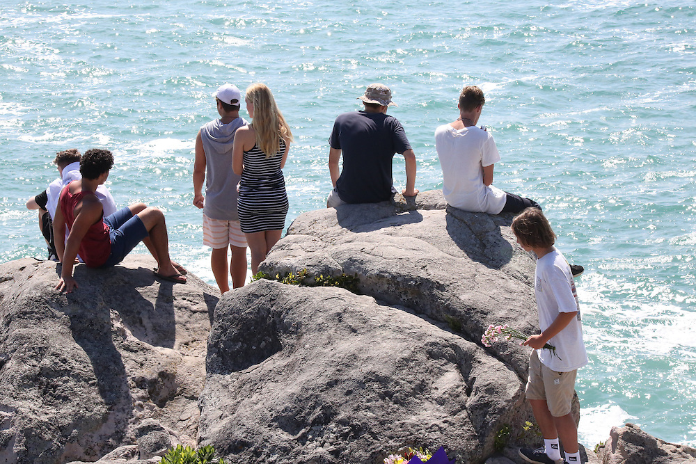Friends of drowned teenager Hamish Rieger on rocks above where he was swept into raging seas by a large wave at Moturiki (Leisure) Island, Mount Maunganui, on Saturday afternoon, Tauranga, New Zealand, Monday, January 25, 2016. Credit:SNPA / Richard Moore
