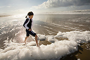 9 year old Isabel Durham plays in sea foam whipped up by the wind at the Oregon Coast. (Fully released - 111106)