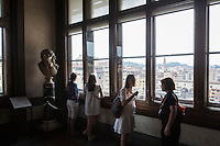 FLORENCE, ITALY - 29 JUNE 2016: Visitors are here by a window overlooking the Vasari Corridor and the Arno river, at the Uffizi Gallery in Florence, Italy, on June 29th 2016.<br /> <br /> Art historian Eike Schmidt, former curator and head of the Department of Sculpture, Applied Art and Textiles at the Minneapolis Institute of Arts, became the first non-Italian director of the Uffizi in August 2015, replacing Antonio Natali who directed the gallery for 9 years. One of the main goals of the new director is to open the Vasari Corridor to the general public. Currently the corridor can only be visited with group reservations made by external tour and travel agencies throughout the year.<br /> <br /> The Vasari Corridor is is a 1-kilometer-long (more than half mile) elevated enclosed passageway which connects the Palazzo Vecchio with the Palazzo Pitti, passing through the Uffizi Gallery and crossing the Ponte Vecchio above the Arno River, in Florence. The passageway was designed and built in 1564 by Giorgio Vasari in only 6 months to allow Cosimo de' Medici and other Florentine elite to walk safely through the city, from the seat of power in Palazzo Vecchio to their private residence, Palazzo Pitti. The passageway contains over 1000 paintings, dating from the 17th and 18th centuries, including the largest and very important collection of self-portraits by some of the most famous masters of painting from the 16th to the 20th century, including Filippo Lippi, Rembrandt, Velazquez, Delacroix and Ensor.