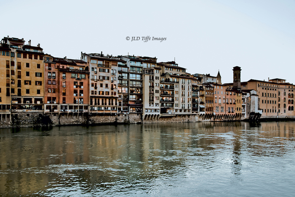 Florence, Arno river, view of apartments and shops along the river bank, reflected in the water.