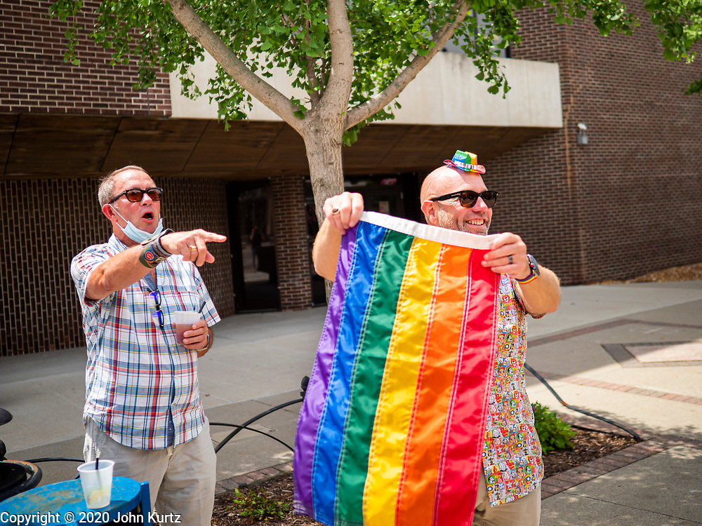 "28 JUNE 2020 - DES MOINES, IOWA: Spectators cheer at the Capitol City Pride Parade in Des Moines. Most of the Pride Month events in Des Moines were cancelled this year because of the COVID-19 pandemic, but members of the Des Moines LGBTQI community, and Capitol City Pride, the organization that coordinates Pride Month events, organized a community ""parade"" of people driving through the East Village of Des Moines displaying gay pride banners and flags. About 75 cars participated in the parade.     PHOTO BY JACK KURTZ"