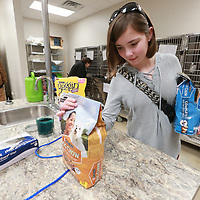 Gabi Clayton, 12, of Mantachie sets out a couple of bags of puupy food at the Tupelo Lee Humane Society that she received as birthday gifts with the sole purpose of donating the items to the shelter. Clayton did this two years for the shleter in Fulton but she wanted to help the Tupelo shelter because as she says