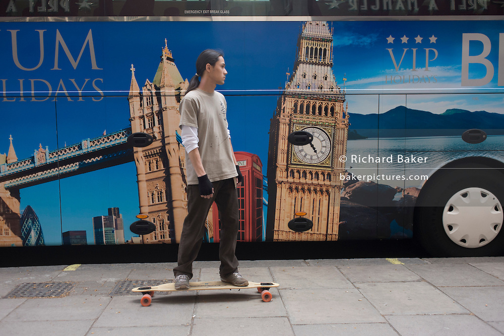 A parked tour coach for Platinum Holidays features famous London landmarks as a young skateboarder rides past.