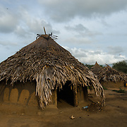 "Simon Jackson's home in the village of Kudo in Eastern Equatoria in South Sudan on 8 August 2014. Jackson says he was unable to farm this year due to illness—""Alas, it has caused me problems""—leaving himself and his wife and their eight children in a precarious position. Unemployed, he says, ""You find any opportunity out there, and you make small money and you buy food for the children. I hustle and I take any small, small jobs I can find. If wasn't sick, I would have been able to farm, and I would have food."" At times, when he cannot find work, he is forced to borrow: ""I find somebody who had a good harvest and borrow from them. If I took a bowl, I return a bowl, if I took ten bowls I return 10 bowls."" Simon received sorghum, vegetable and maize seeds to plant during a Plan International distribution. Asked what he will do with his future harvest, he replies, ""Why would anyone in their right mind eat everything? You eat some, and you keep some. I will do my best, and whatever God blesses us with we will use it, and we will keep some. But I have no guarantee."""