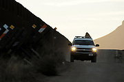 A U.S. Border Patrol agent drives on a dirt road along the U.S./Mexico border wall near the San Pedro River, Cochise County, Hereford, Arizona, USA.