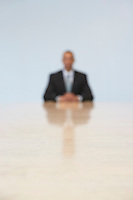 Business man sitting at end of conference table (defocused)