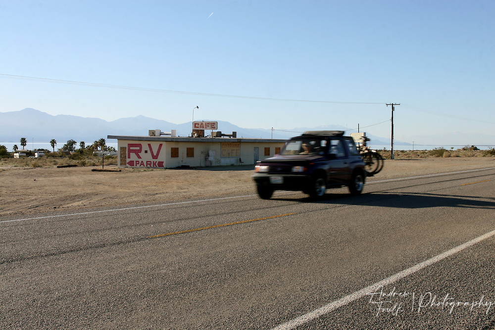 Andrew Foulk/For High Country News.An SUV drives south on highway 111 the main through-fair on the eastern side of the sea. Behind it lay the closed down remnants of the Corvina Cafe a onetime stop for those taking the same route.