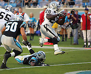 CHARLOTTE, NC - NOVEMBER 7:  Running back Amos Zereoue #28 of the Oakland Raiders leaps over a defender to score on a seven yard touchdown run in the fourth quarter against the Carolina Panthers at Bank of America Stadium on November 7, 2004 in Charlotte, North Carolina. The Raiders defeated the Panthers 27-24. ©Paul Anthony Spinelli  *** Local Caption *** Amos Zereoue