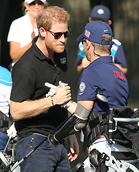 Prince Harry Attended the Invictus inaugural golf tournament at St Georges Golf course Toronto and congratulated triple amputee Micheal Nicholson on a superb tee off from the 16th tee<br />