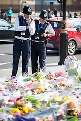 © Licensed to London News Pictures. 27/03/2017. London, UK. Police officers pay their respects to the victims of Westminster terror attack outside the Houses of Parliament in London on Monday, 27 March 2017. Photo credit: Tolga Akmen/LNP