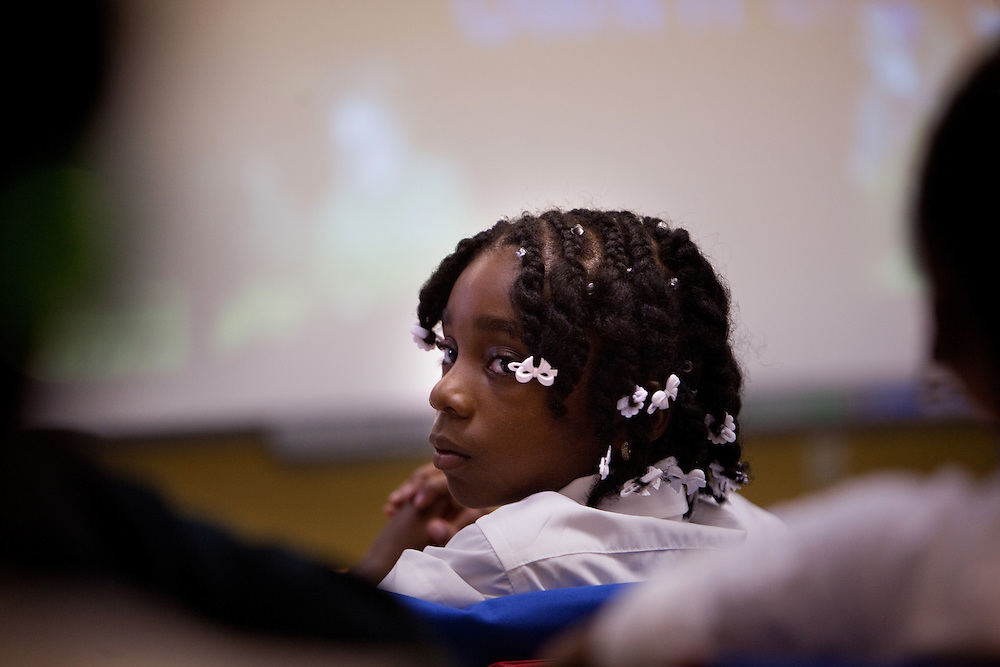 Third-grade student Mya (?) listens as a student answers a question on the first day of class at Brownsville Elementary School in Brooklyn, NY on August 15, 2011.