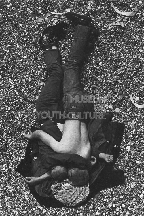 Skinhead couple lying on the beach in Brighton