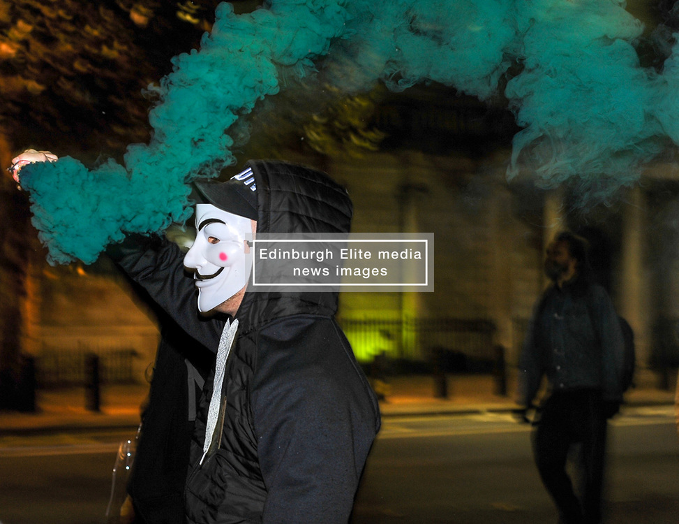 A protester lets off a smoke canister during the annual 'Million Mask March' demonstration as they walked down Whitehall. London, 05 November 2018.