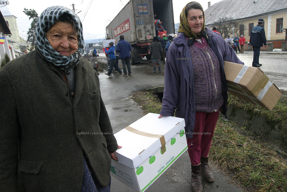 A german truck column deliver thousands of parcels after christmas to deserving poor in romanian villages. people wait and stands a line to get one of parels containing food and small presents to the kids.