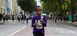 London, August 30th 2015. A little boy enjoys his ice cream as revellers enjoy Family Day at the Notting Hill Carnival.