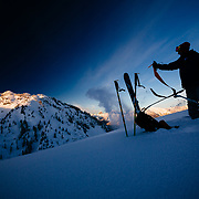Tyler Hatcher skins up for another run in the Cascade backcountry in the early evening light.