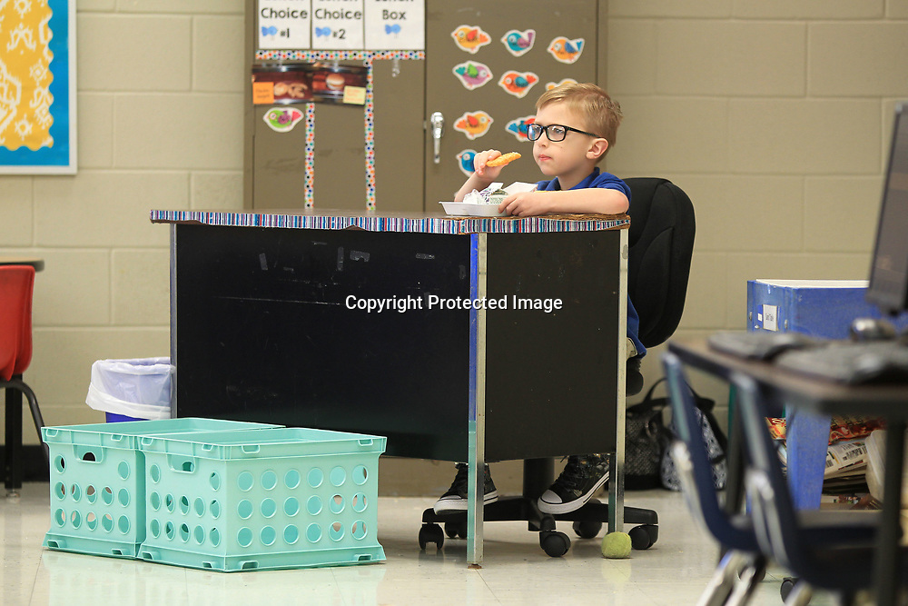 Thomas Greenlee, 6, a first grader at Saltillo Primary School, sits at in his mothers room and eats his breakfast before getting his first day of school started on Thursday morning.