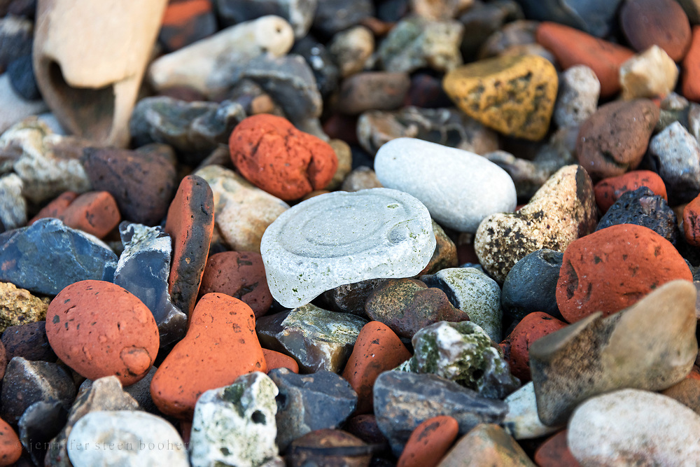 A sea glass bottle bottom amoung fragments of brick, chalk, and flint on the Thas foreshore, Greenwich, London.