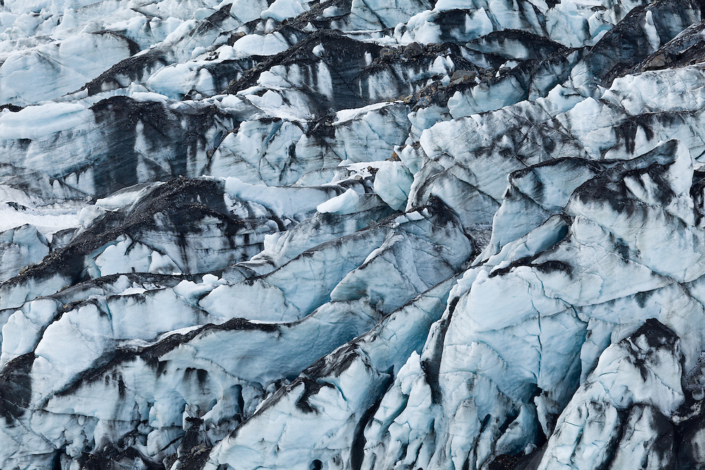 Pressure ridges and rock debris create layers in the face of Childs Glacier in the Chugach Forest of the Copper River Delta in Southcentral Alaska. Spring. Afternoon.